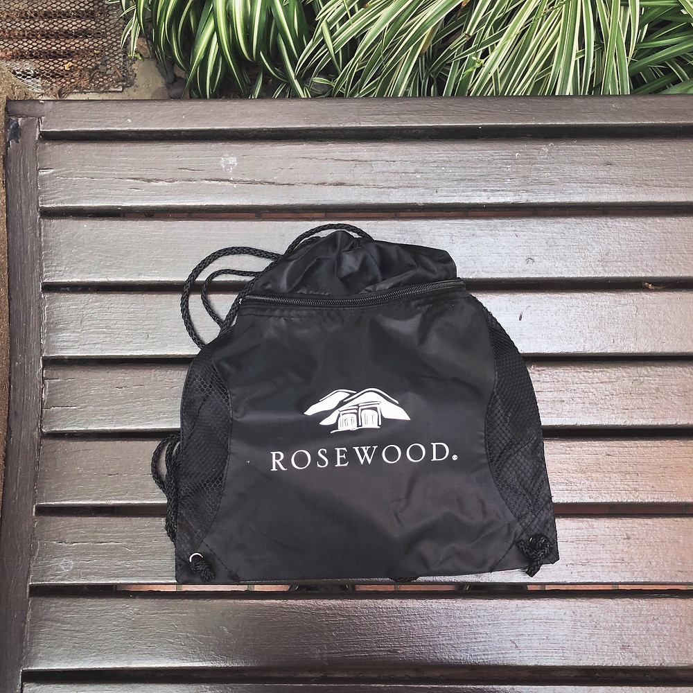 "A black mesh sports bag with the word ""Rosewood"" in white serif font printed on the front, along with an icon of white hills and a house. It lays flat on a dark brown slatted-wood bench. A leafy green plant overflows onto the top of the image."