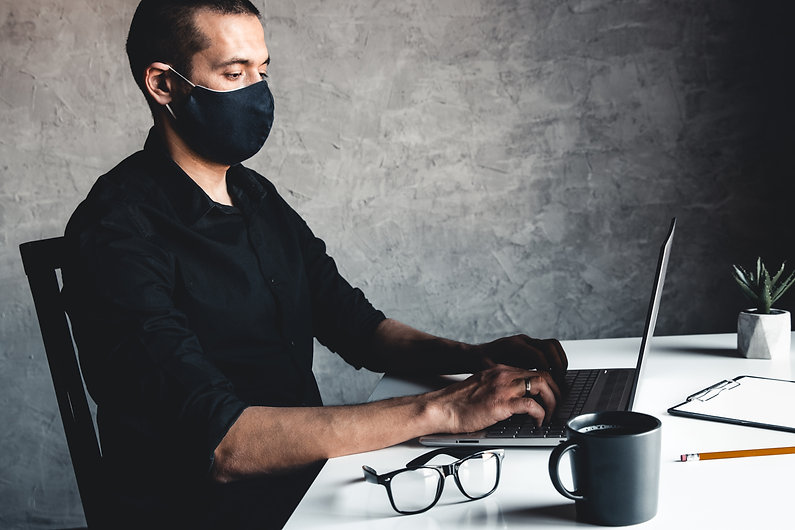 a-masked-man-works-at-a-computer-pandemi