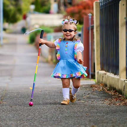Young girl using a rainbow coloured long cane on a street