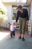 Toddler using a long cane whilst being guided by O&M specialist Bronwen Scott