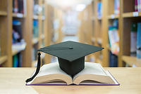 graduation cap over open Books on Librar