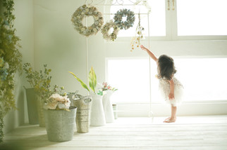 1才女の子が白い部屋で花を触っているかわいい写真。誕生日