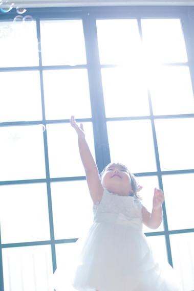 1才女の子が白いワンピースを着て手をあげている写真