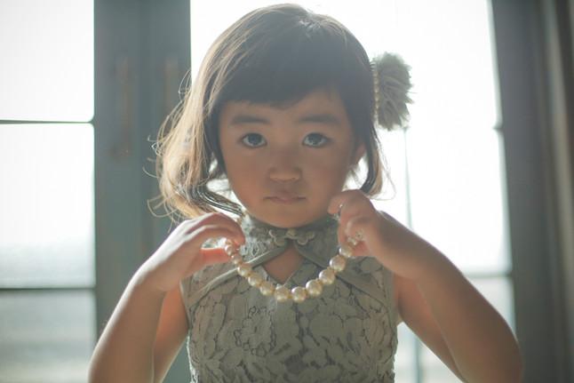 3才女の子がグリーンのドレスを着てネックレスをつけてしっとり前を見てる写真