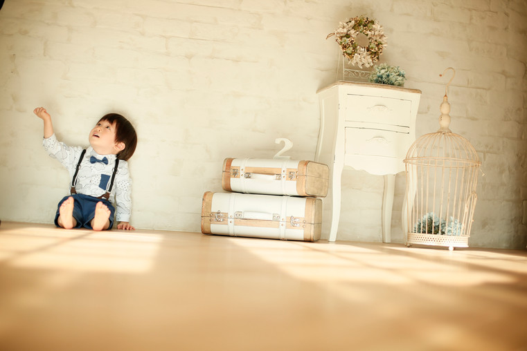 1才男の子がシャツを着て床に座って手を上げている誕生日の写真