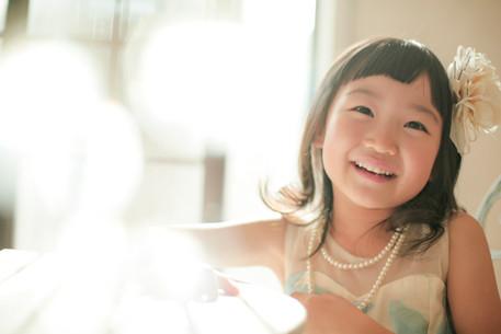 5才女の子が木のテーブルに手を置いてやさしく微笑んでいる写真
