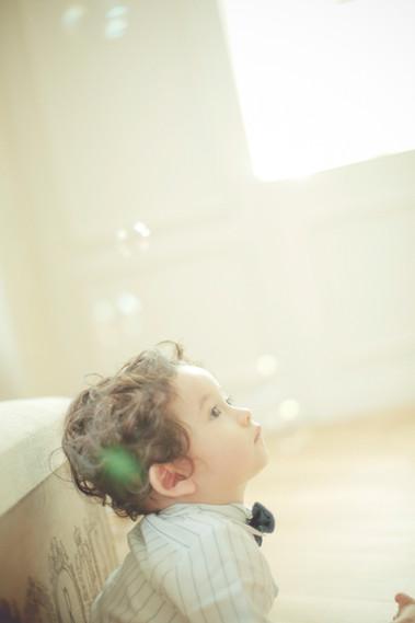 1才男の子、温かみのある部屋でシャボン玉を見てる写真