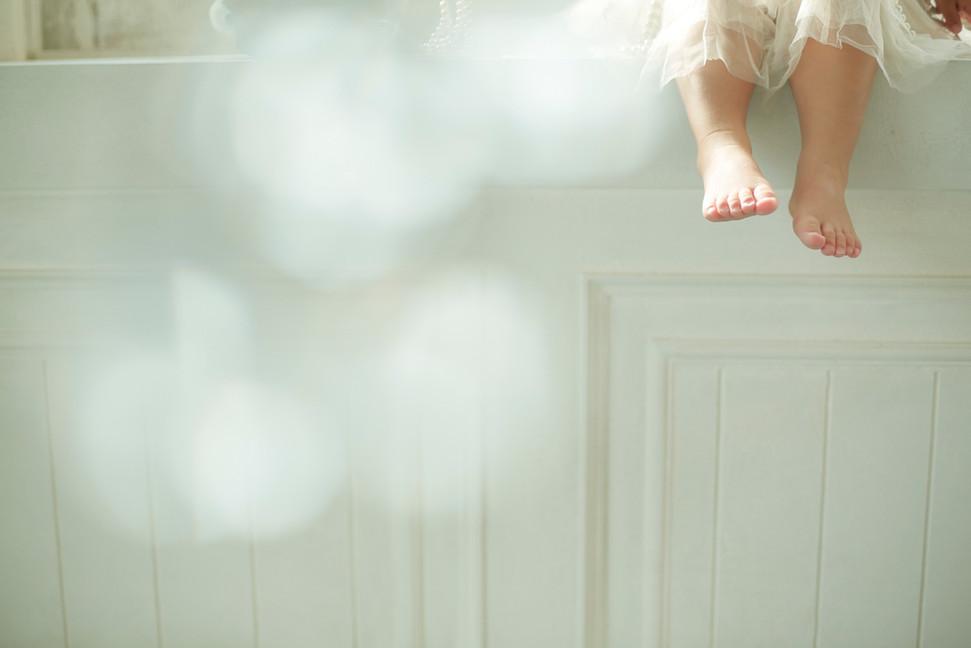 1才女の子が白い棚に座っているかわいい足の写真。誕生日