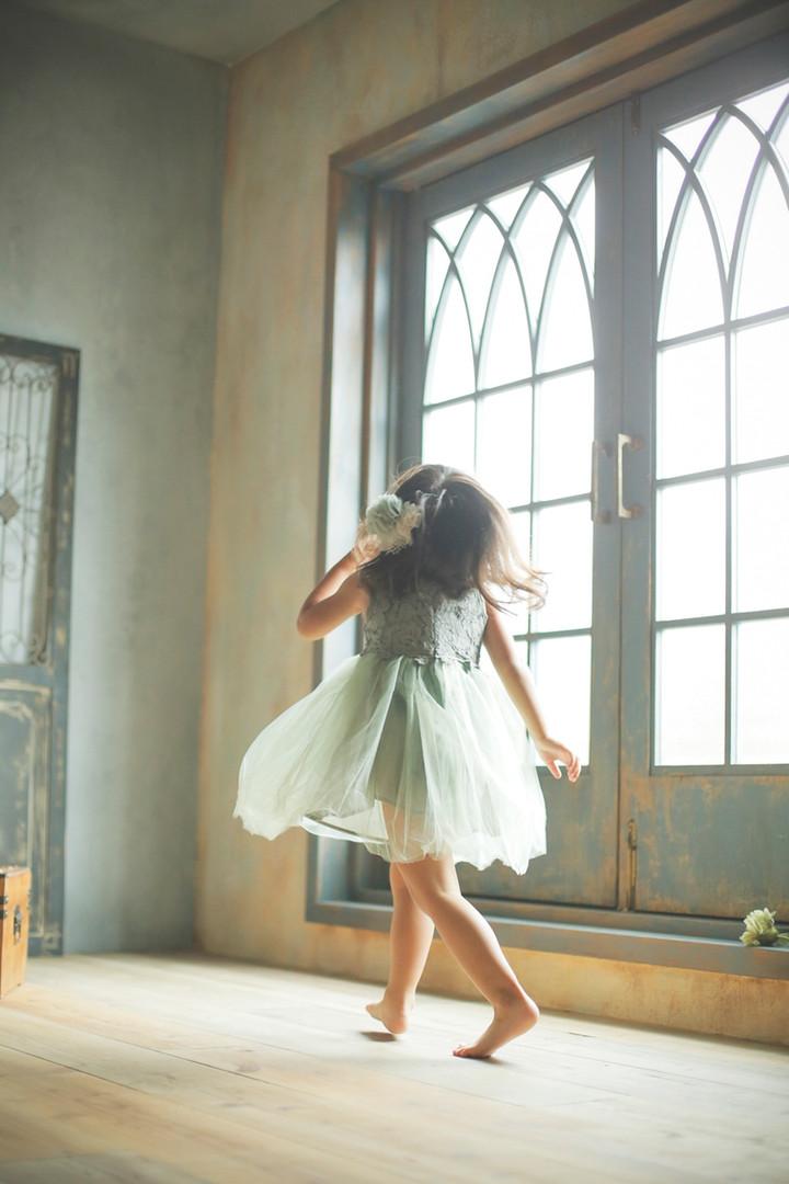 3才女の子がグリーンのドレスを着て楽しそうに歩いてる写真