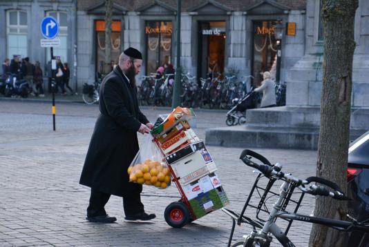 In Amsterdam zie je dit absoluut niet meer, zo'n orthodoxe Joodse man. Vanwege de agressie richting Joodse mensen is dit straatbeeld daar verdwenen. Deze foto is genomen in Maastricht. Het is vrijdagmiddag, en dit zijn de inkopen voor de sabbat.  Ik vind deze man ontzettend moedig, dat hij op deze manier op straat zijn geloof in zijn kleding uitdraagt.