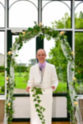 officiant  de ceremonie relisant ses textes devant son pupitre avec arche fleurie et déco florale composée de roses blanches marguerites fresias lys blancs.