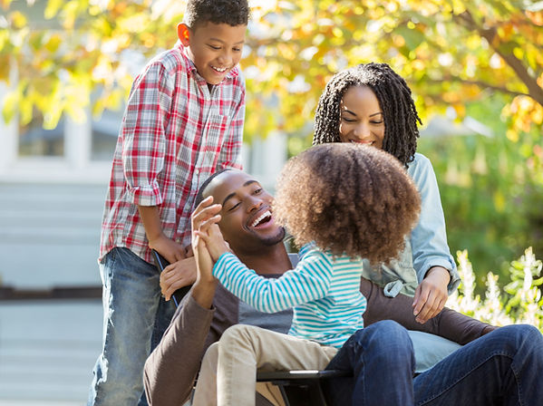 Stock photo of a black family of four laughing and playing together in their yard