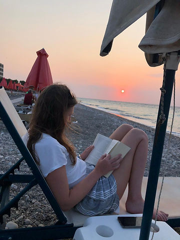 Jennie is sat reading a book on the beach at sunset