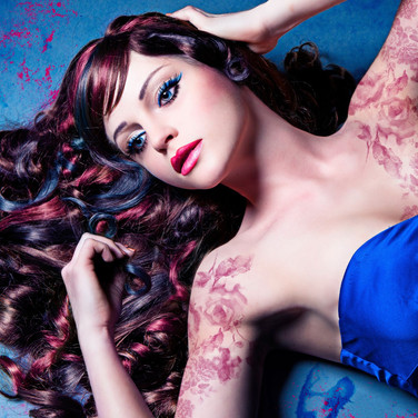 Reclining woman with long dark red curls and red tattoo
