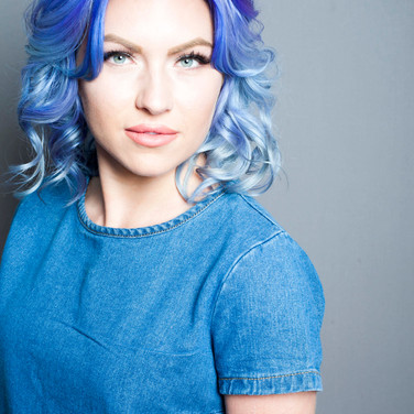 woman with dark blue to light blue ombre curls