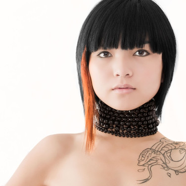 Woman with black assymetrical bob and orange highlight