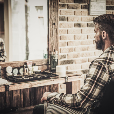 Man with beard and parted short hair looking in a mirror