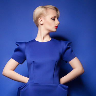 Woman with short blonde hair and blue dress