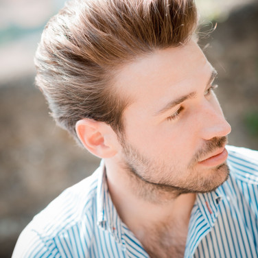 Man with swept back hair unshaven
