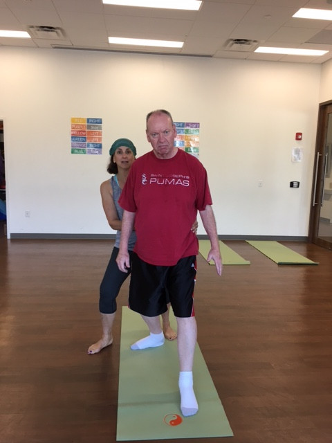 Chuck prepares for his warrior with YogaReach instructor Nancy Aeder.