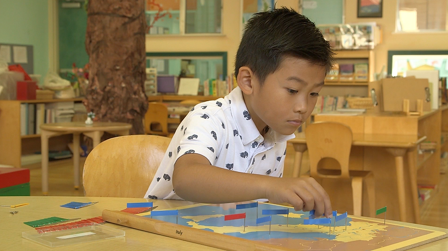Montessri elementary student works on a flag map of Italy