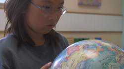 Girl looking at globe of the world