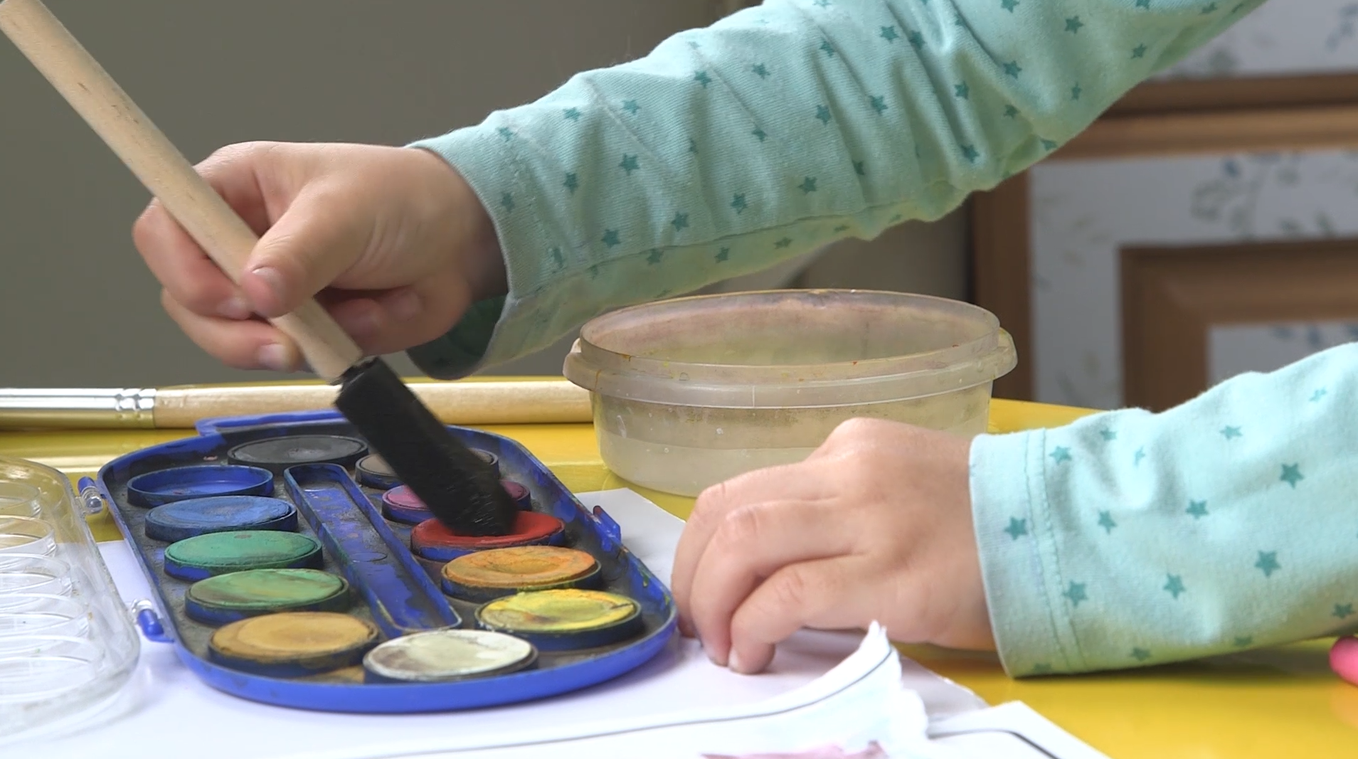 Young child paints with watercolors