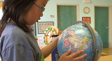 A young girl examining a globe model of the earth