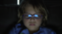 Young child gazing at an iPad, reflection on his glasses