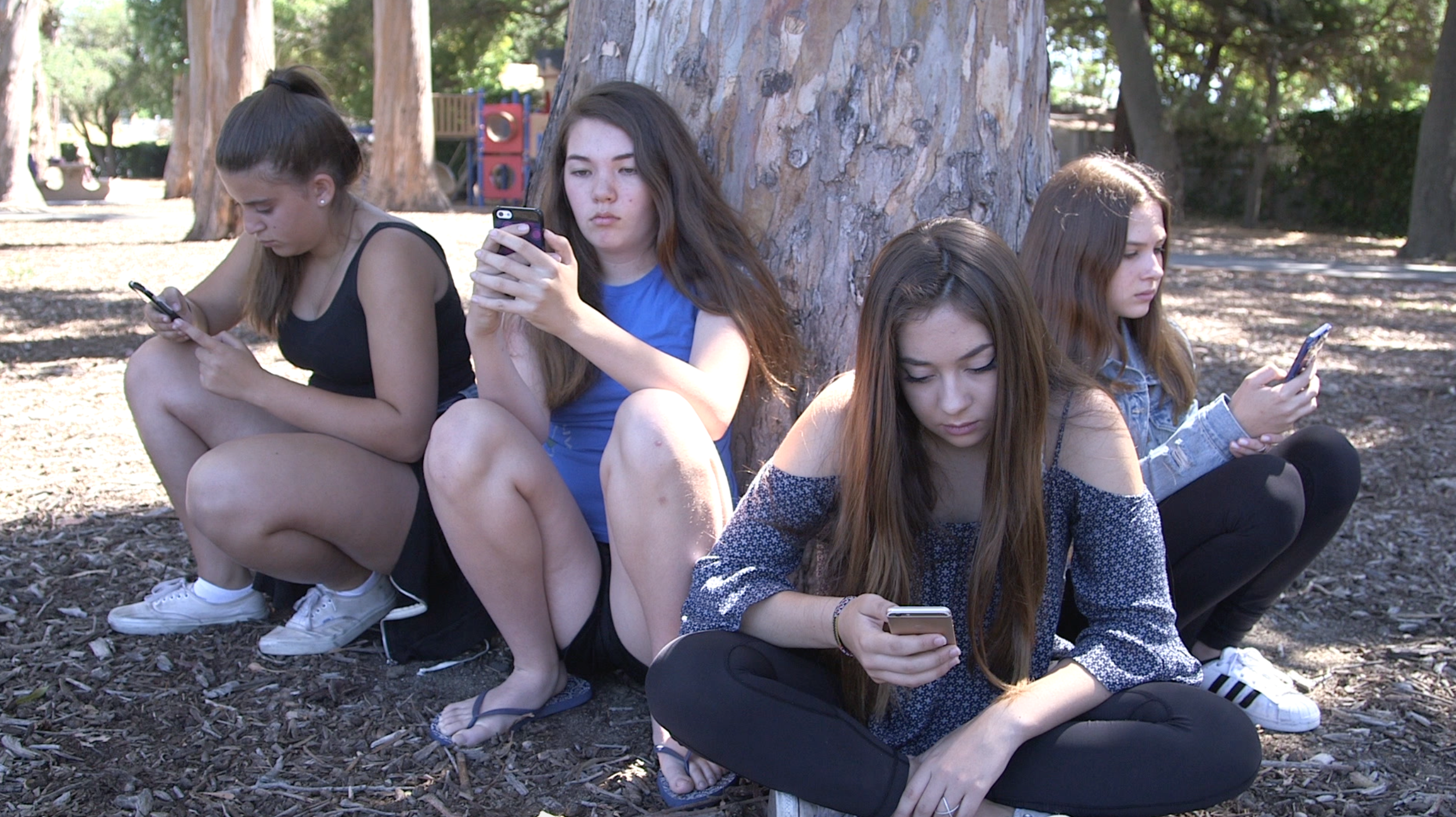 Teenagers looking at their phones