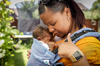 A black woman in looking doen at her newborn baby being carried in a blue and purple buckle carrier on her front. He is holding her finger. They are in a garden.