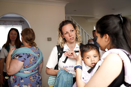 A white woman with brown and blonde curly hair is in the centre facing the camera. She is talking to a lady with dark brown hair who is side on to the camera. This lady is babywearing her baby on her front in a purple baby carrier. The baby has black hair and is looking at the camera. To the left of the picture two white women are talking, one has brown hair and is facing the camera, the other has red hair, a flowery dress on, is wearing a stretchy wrap and has her back to the camera.