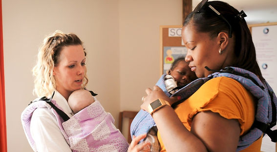 A white woman on the left carrying a doll in a buckle carrier on her front. She is helping a black lady on the right who is carrying her newborn baby in a buckle carrier on her front.