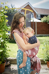 A white woman with long brown curly hair looking down at her child who is carried in a red and white woven wrap on her front. Her child is breastfeeding. They are in a garden.