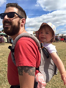 A white man wearing sunglasses with short brown hair is back carrying a 2 year old white child with a hat on, in a grey buckle carrier. They are in a field, you can see the grass and sky behind them.