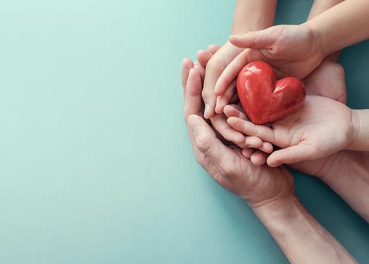 adult-child-hands-holding-red-heart-aqua