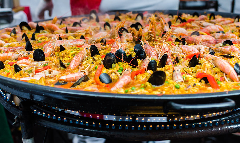 Seafood paella in a paella pan at a stre