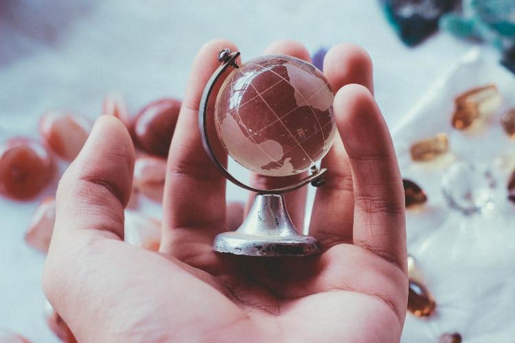 Mini mappamondo in una mano, su sfondo chiaro.