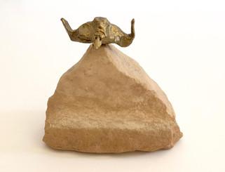bronze head lands on stone