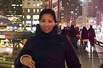 woman in city scene wearing black coat