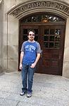 man in front of wooden double doors