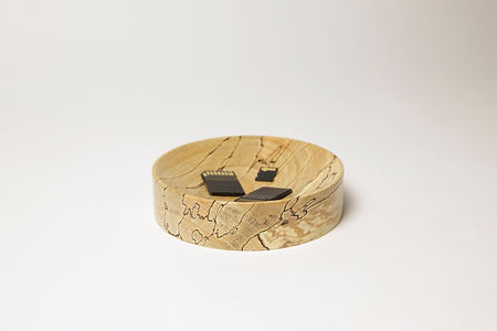This series of minimalistic designed bowls by Milo Dool serve as pedestal to arrange everyday objects. Wooden bowl with SD cards.