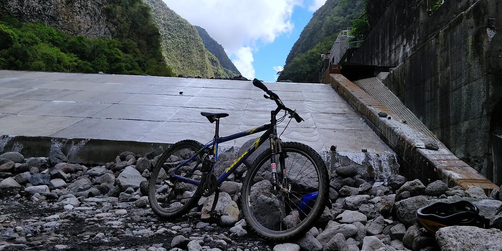 Photo vélo VTT MBK 26 pouces sur le sentier des Gorges de la Plaine à La Runion, ciel bleu et montagne