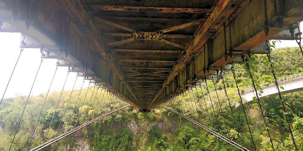Photo du dessous du pont-suspendu de la rivière de l'est à l'île de La Réunion. Des câbles soutiennent des immenses poutre de fer.
