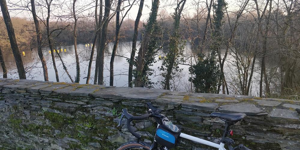 Vélo appuyé contre un muret avec une retenue d'eau en fond