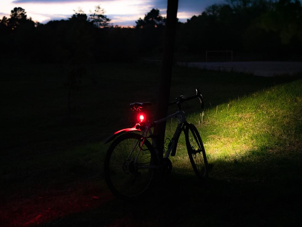 Vélo dans le noir avec un éclairage rouge arrière et un éclairage blanc avant