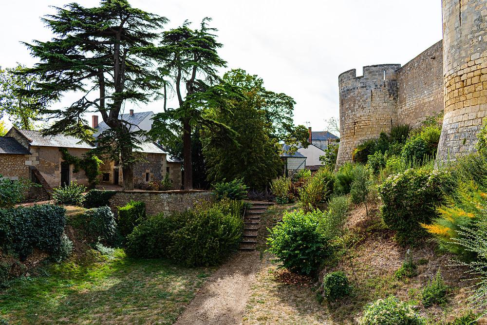 Anciennes douves du châeau, transformé maintenant en jardin, une batisse en pierre à gauche avec deux connifère et les tours du château à droite de la photo