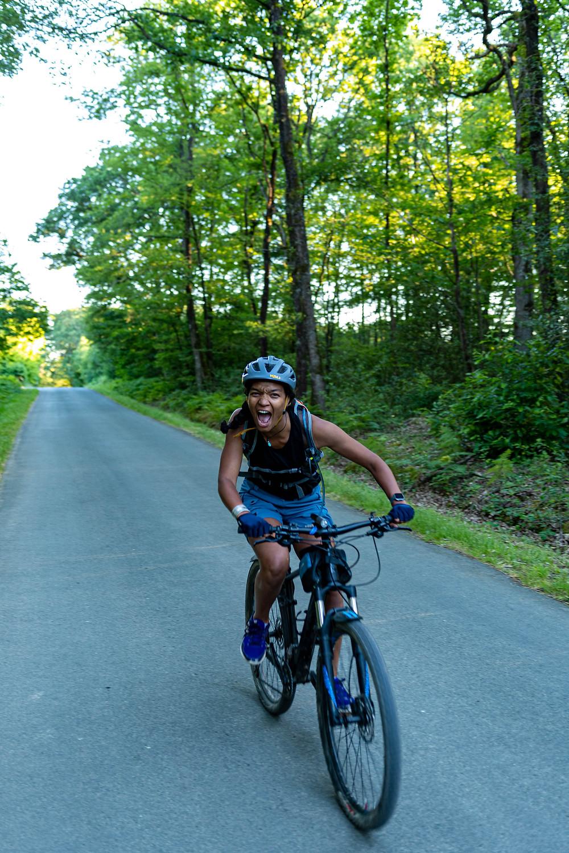 Une personne sur son vtt, casque gris, VTT cube reaction pro sur la route à côté de la forêt