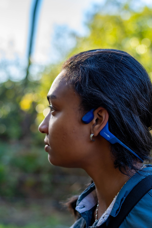 Photo d'une femme de profil avec un casque audio Aftershokz de la marque Aeropex