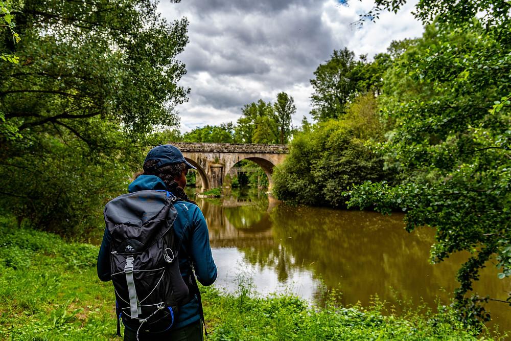 Photo d'une femme de dos en tenue de randonnée avec vue sur le pont du Pont Barré à Beaulieu-sur-Layon en Anjou